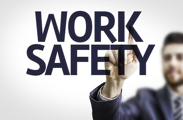 Business man pointing to transparent board with text Work Safety-1
