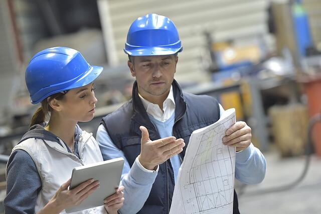 Engineers in mechanical factory reading instructions.jpeg
