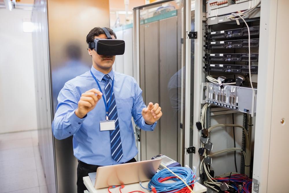 Technician using visual reality headset in server room.jpeg