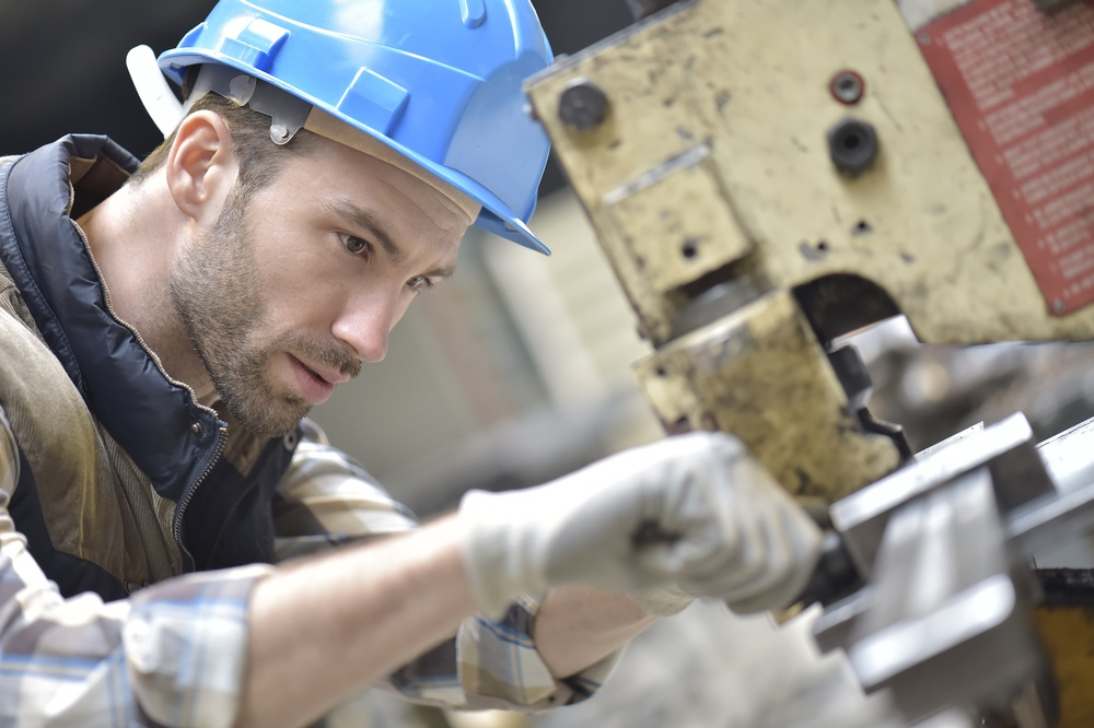 Industrial worker working on machine in factory.jpeg